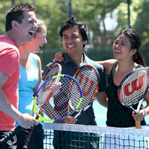 4 people on a tennis court chatting